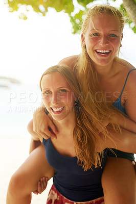 Buy stock photo Portrait of an attractive young woman piggybacking her friend on the beach