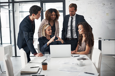 Buy stock photo Cropped shot of a group of businesspeople using a laptop during a meeting in an office