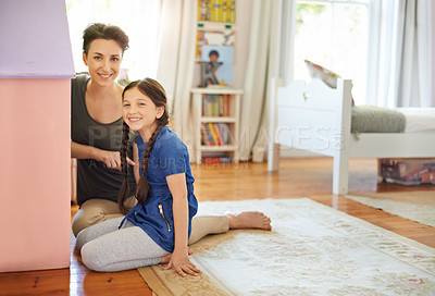 Buy stock photo Portrait of a young mother and her daughter playing with a dollhouse