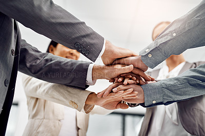Buy stock photo Low angle shot of a group of businesspeople standing with their hands in a huddle