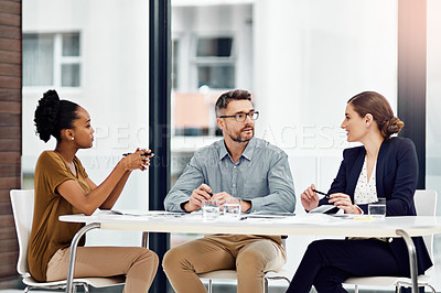 Buy stock photo Cropped shot of three businesspeople working together in their office