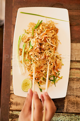 Buy stock photo Shot of a person eating a bowl of pad thai in a restaurant in Thailand