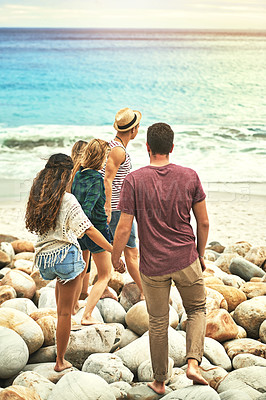 Buy stock photo Rearview shot of two couple walking down to the water at the beach