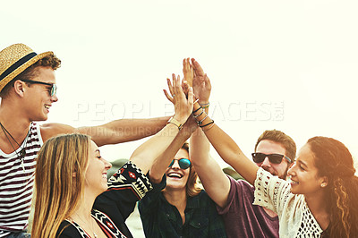 Buy stock photo Cropped shot of a happy group of friends high fiving on the beach