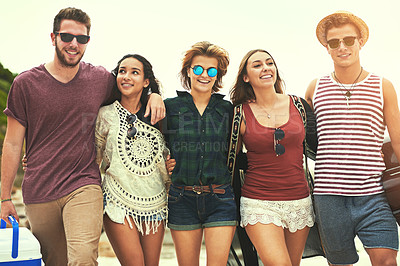 Buy stock photo Cropped shot of a group of friends walking on the beach on a summer's day