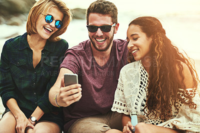 Buy stock photo Cropped shot of a young man showing two female friends something on his cellphone