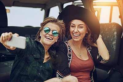 Buy stock photo Cropped shot of two young friends taking a selfie while on a roadtrip together