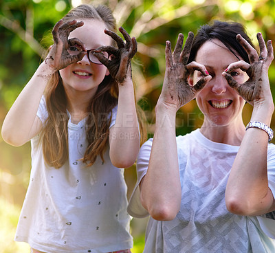 Buy stock photo Portrait of a mother and her little daughter covering their eyes with their muddy hands outside
