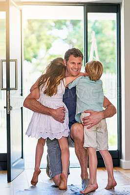 Buy stock photo Shot of a father embracing his two little children as he enters the house