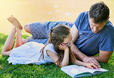 Buy stock photo Shot of a father and his little daughter reading a book together on the grass outside