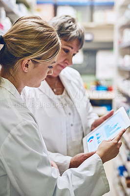 Buy stock photo Shot of pharmacists using a digital tablet together