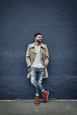 Buy stock photo Shot of a fashionable young man wearing urban wear and posing against a gray wall