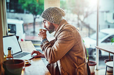 Buy stock photo Shot of a handsome young man sitting at a cafe counter using a laptop and drinking a cup of coffee