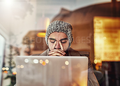 Buy stock photo Shot of a young man looking stressed while using a laptop in a cafe
