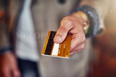 Buy stock photo Cropped shot of an unrecognizable young man handing over a credit card in a shop