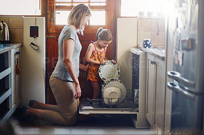 Buy stock photo Shot of a mother and her little daughter using a dishwashing machine at home