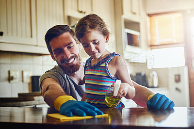 Buy stock photo Cropped shot of a father and his little daughter cleaning a kitchen surface together at home