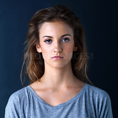 Buy stock photo Studio shot of an expressionless teenage girl posing against a dark background