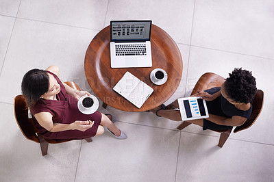 Buy stock photo High angle shot of two businesswomen having a discussion in an office