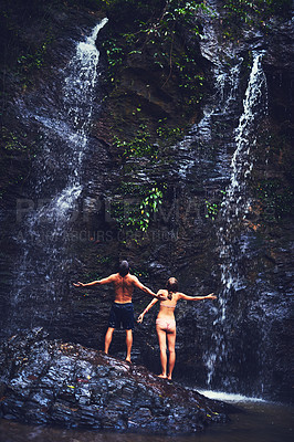 Buy stock photo Rearview shot of a young couple standing under a waterfall in the jungle