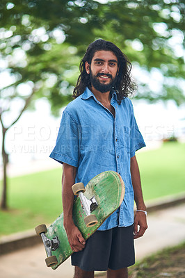 Buy stock photo Portrait of a smiling young man carrying a skateboard standing outside on a sunny day