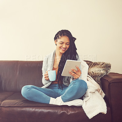 Buy stock photo Shot of a young woman relaxing at home with a cup of coffee and a digital tablet