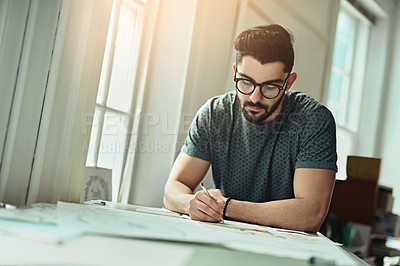 Buy stock photo Cropped shot of a handsome young designer working on a drafting table in the office