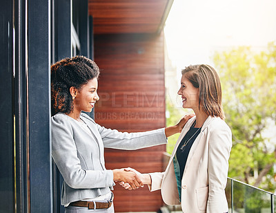 Buy stock photo Shot of two businesswomen shaking hands outside an office