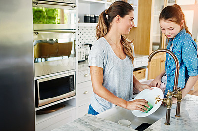 Buy stock photo Shot of a young mother washing dishes at home while her daughter watches