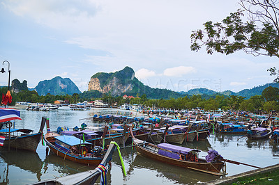 Buy stock photo Shot of traditional wooden boats resting on a beach in Thailand