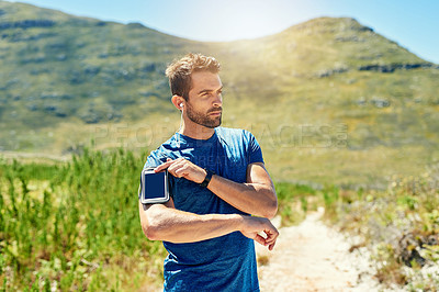 Buy stock photo Cropped shot of a young man listening to music while out for a run