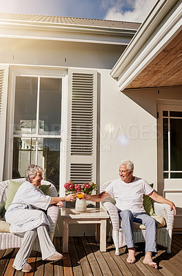 Buy stock photo Shot of a happy senior couple toasting with juice on the patio at home
