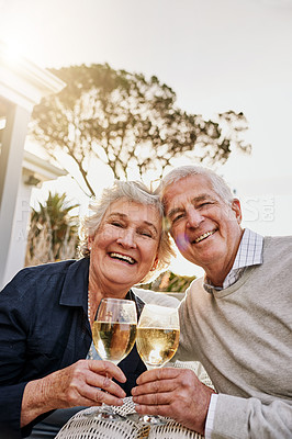 Buy stock photo Shot of a happy senior couple toasting with wine on a leisurely afternoon outside