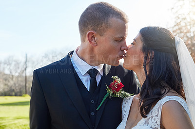 Buy stock photo Cropped shot of a bride and groom kissing on their wedding day