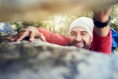 Buy stock photo Portrait of a happy hiker climbing over rocks on a mountain trail