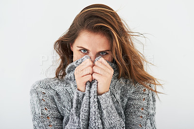 Buy stock photo Studio portrait of a young woman hiding under her wooly sweater against a light background