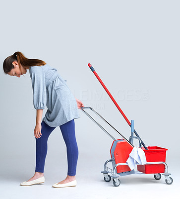 Buy stock photo Portrait of a tired young female pulling trolley against grey background