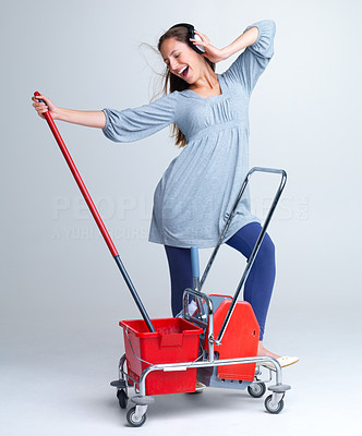 Buy stock photo Excited young woman listening to music on headphones while holding a cleaning trolley against grey background