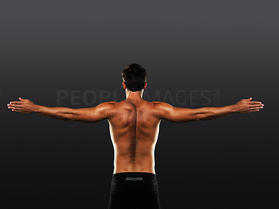 Buy stock photo Rear view of healthy muscular man stretching his arms and exercising on black background