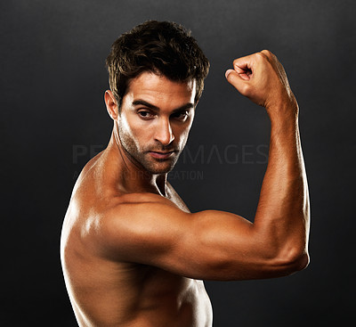 Buy stock photo Young man showing off his biceps on black background