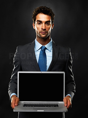Buy stock photo Portrait of young business man standing on black background and showing you his laptop