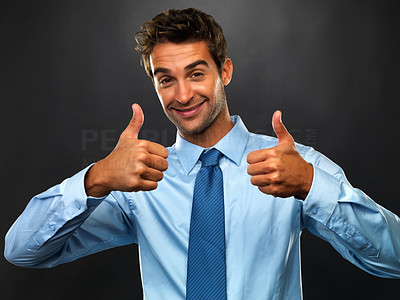 Buy stock photo Portrait of young business man smiling and giving you two thumbs up on black background