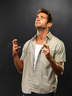 Buy stock photo Young man with eyes closed crossing his fingers in anticipation on black background