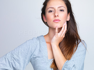 Buy stock photo Closeup portrait of a beautiful young woman posing against grey background