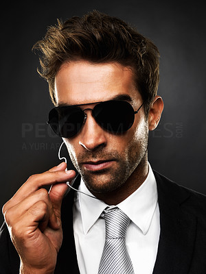 Buy stock photo Closeup of a stylish secret service agent holding up the wire to his ear-piece, against a dark background