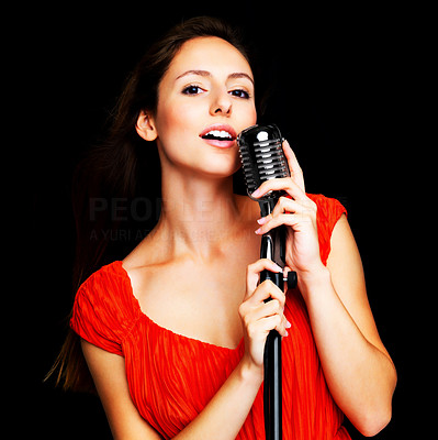 Buy stock photo Portrait of a beautiful young jazz singer using her vintage microphone