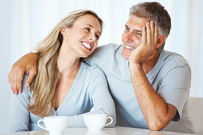 Buy stock photo Portrait of mature couple in love having cup of tea together indoors