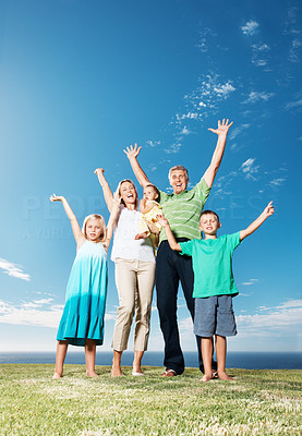 Buy stock photo Full length of happy family raising their hands up together at park