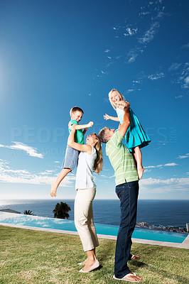 Buy stock photo Full length of parents lifting their children up at park