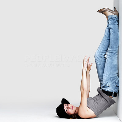 Buy stock photo Portrait of a crazy young woman posing in upside down posture against grey background - Copyspace